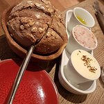 Fresh warm bread with butter, pork rillettes and oil.