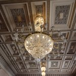 A magnificent chandelier hangs from an exquisitely detailed ceiling
