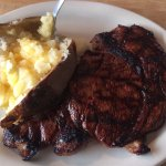 Large rib eye medium rare with baked potato with butter