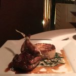 The quail appetizer is served with creamed spinach and a mushroom risotto cake. and
