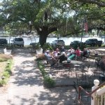 outdoor seating under live oaks, view of river