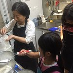 Ivy showing my daughters how to sift the flour. She provides great aprons.