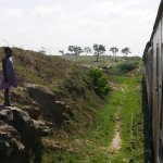 Child in village near Mombasa looking at the train slowly passing by