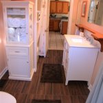 Bathroom with tub and shower; doors to bedroom, kitchen, and outdoor shower