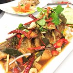 PLA LUI SUAN is deep fried sea bass top with homemade sauce and mixed thai herbs