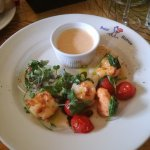 Pan-fried king prawns with chilly, garlic, cherry tomatoes, spinach and coriander, served with c