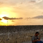 Sunset behind the wall. This young man was playing steel drum