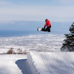 Snowboarder riding terrain park jump with view of Sea of Japan. Photo by Keith Stubbs.