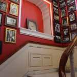 Staircase decorated with pictures of royal family members.