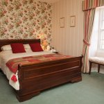 Fern bedroom with king size sleigh bed.