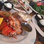 lobster tail and ribeye with baked potatoes