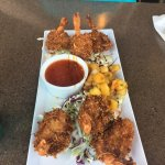 Coconut Shrimp appetizer portion on delicious cabbage with sweet chili dipping sauce and mango s