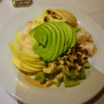 A nice salad with avocado, veggies, fruit and nuts.
