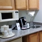 small kitchen area with sink,coffee maker, fridge and microwave