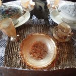 The dining table still displays the superb china and glassware from ancient past.