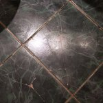 Cracked tiles on bathroom floor in premium room