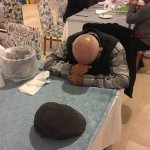 owners uncle being sick in dinning room , sick bucket on table