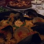 Seafood paella, octopus, and a glass of vinho verde