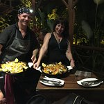 The owners bring our paellas!