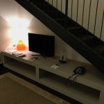 TV under the stairs to the bedroom