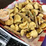 Appetizer platter with fried pickles, fried green beans & Cajun fries.