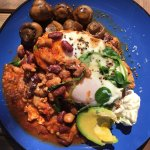 Pan baked eggs in spicy beans with mushrooms on the side
