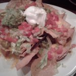 nachos with sour cream, peppers and guacamole.