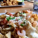 Seafood Nachos in the foreground, and clam strips in the distance, a gin and tonic riding shotgu
