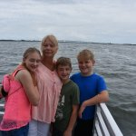 Grandma and grandchildren are all smiles after a family day on the water