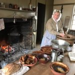 In one of the replica farmhouses, a woman was using the brick oven and fireplace to prepare food