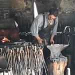 The blacksmith is shaping the hot metal.