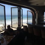 View of the ocean and the beach from the high tables at the back end to the bar.