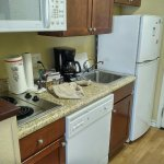 Full kitchenette with dishwasher, plates, glasses, pans, silverware