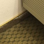 Stick down vinyl in bathroom  with pink tile, the floor is tilted, clean older motel.