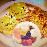 Eggs benedict with fruit salad and hash browns