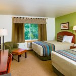 Grande Double room from entrance. Rooms feature chair, ottoman, desk, flat screen TV, coffee mak