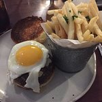 the burger with egg on top and fries