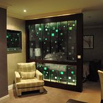 Room at night with illuminated glass wall between bed/sitting area.