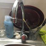 Baño descuidado, viejo, roto, desconchado, descuidado, grifo de la 'cocina' sin agua caliente, s