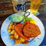 Frankfurt Schnitzel (breaded, pork) with baked potatoes and Frankfurt green sauce with a glass o