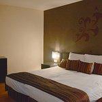 Sovrumsdelen i sviten med en byrå, sängbord och fåtölj (inte i bild)