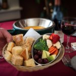 Cheese fondue served with assorted breads and vegetables.