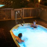 Hot tub at night with pool in the background
