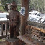 Outside hand carved bench and bear