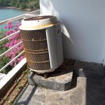 Noisy antiquated air conditioner on dirty balcony