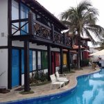 pool, tiki bar at the back, and rooms facing the sea