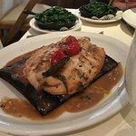 Mediterranean Sea Bass on wood plank, with spinach