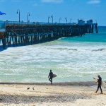 Two surfers walk toward the pier.