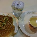 Soft and hard style konafa belgebnah with a sweet syrup and a glass of water