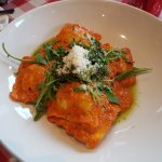 Ravioli with cheese and basil covered in tomato sauce